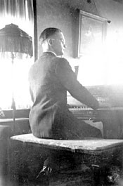 Gerhard Jr. playing Dad's piano, circa mid-1930s, with Theresia's painting of Jesus above piano.