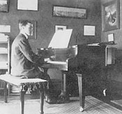Gerhard at his new Chickering baby grand piano, St. Paul, February 1918. His sister Theresia's painting of Jesus hangs above the piano.